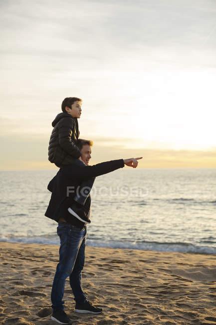 Père portant le fils sur des épaules sur la plage pendant le coucher du soleil — Photo de stock