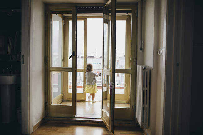 Italy, Naples, back view of little girl standing at door of roof terrace — Stock Photo