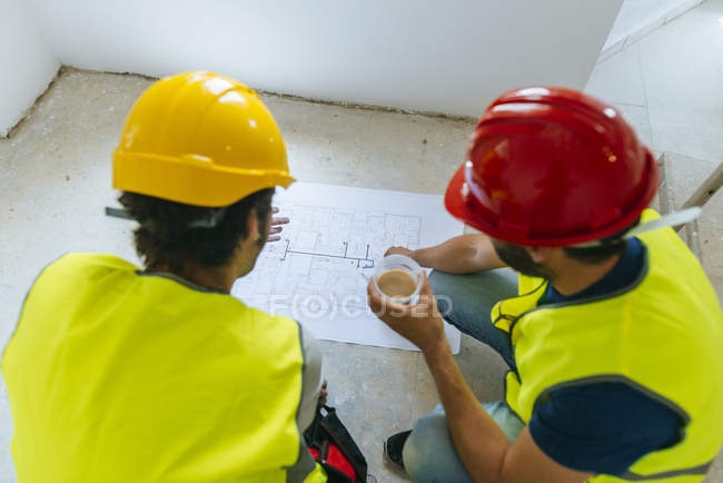 Two workers looking at construction plan — Stock Photo