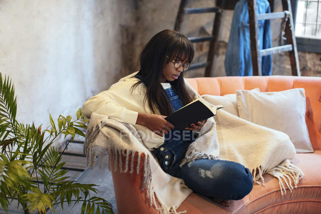 Young woman sitting on the couch at home reading book — Stock Photo