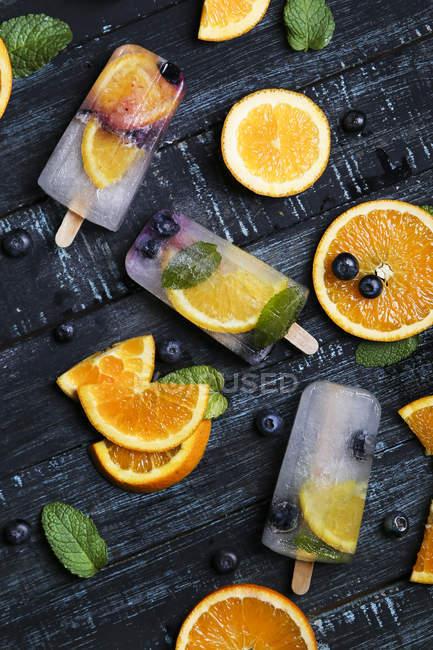 Paletas caseras desintoxicantes con arándanos, rodajas de naranja y hojas de menta sobre madera negra - foto de stock
