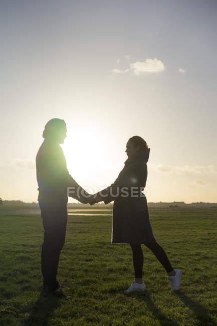 Liebevolles junges Paar steht Hand in Hand auf der Wiese bei Sonnenuntergang — Stockfoto