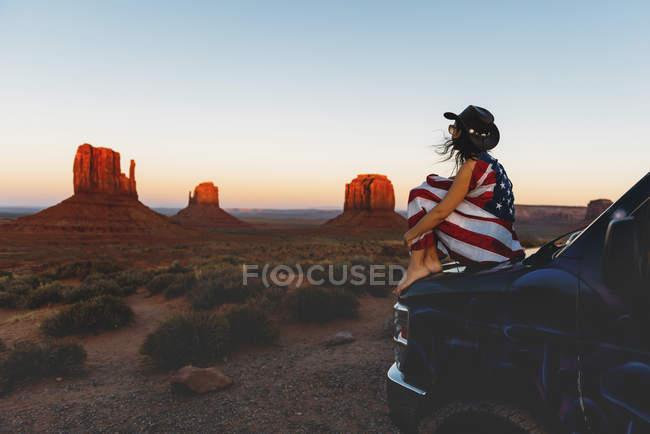 Usa, Utah, Femme battant pavillon des États-Unis d'Amérique et profitant du coucher du soleil à Monument Valley — Photo de stock