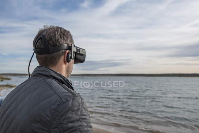 Человек в очках от виртуальной реальности на берегу озера — стоковое фото