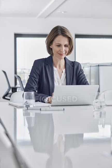 Femme d'affaires utilisant un ordinateur portable au bureau — Photo de stock