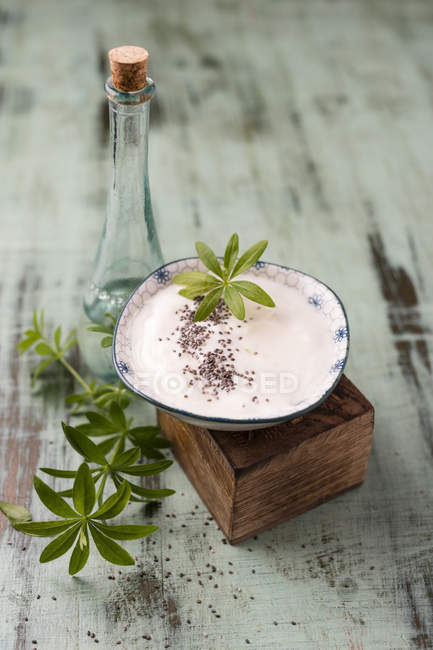 Glass bottle of woodruff sirup and bowl of natural yoghurt with chia and woodruff sirup — Stock Photo