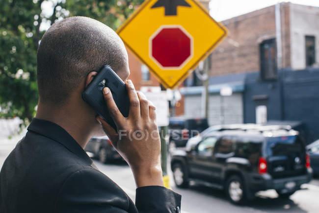 Человек, стоящий у дороги, разговаривающий по телефону — стоковое фото