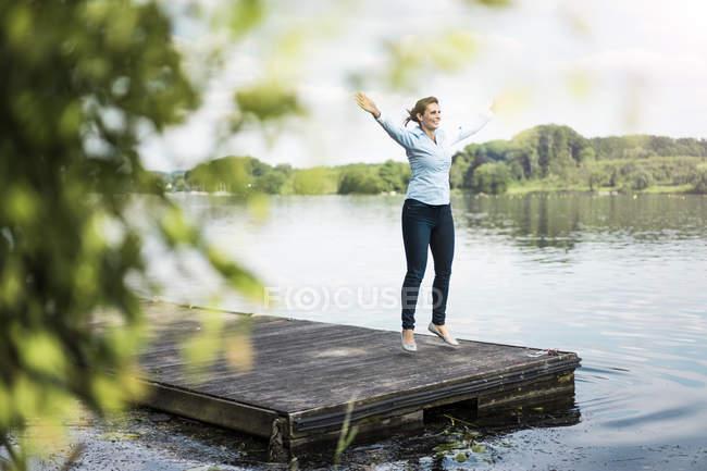 Donna che fa un salto jack su pontile a un lago — Foto stock
