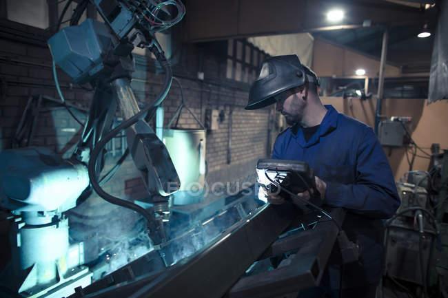 Welder welding metal with robot — Stock Photo