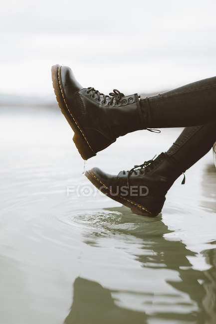 Woman wearing black boots touching water surface of lake, partial view — Stock Photo
