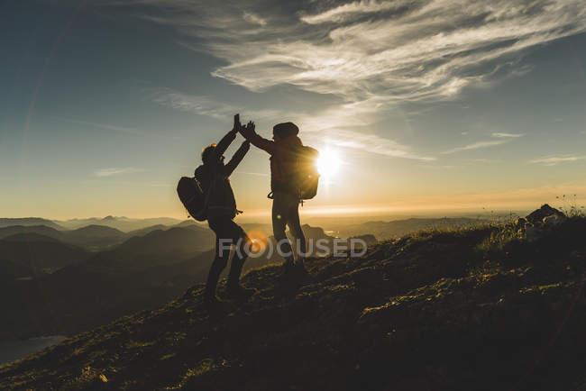 Austria, Salzkammergut, Cheering couple reaching mountain summit — Stock Photo