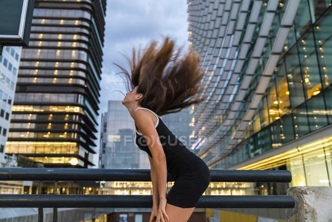 Spensierata giovane donna che indossa abito nero in città al crepuscolo svestirsi i capelli — Foto stock
