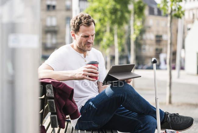 Людина з прокатки валізу і винос кави сидячи на лавці за допомогою планшета — стокове фото