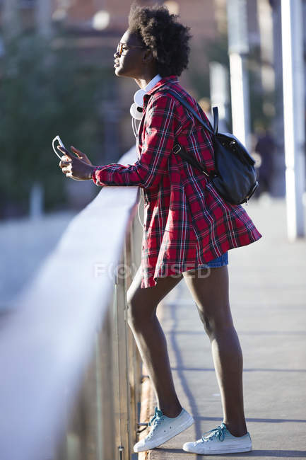 Young woman with backpack standing on a bridge listening looking at distance — Stock Photo