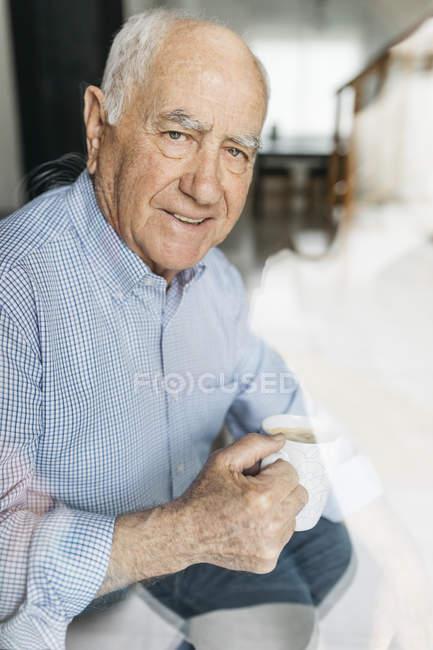 Homme âgé prenant un café tout en se relaxant à la maison, regardant la caméra à travers un verre — Photo de stock