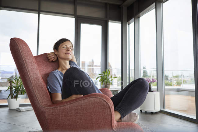 Woman sitting in armchair at home relaxing with closed eyes — Foto stock