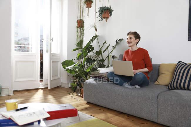 Frau sitzt auf Couch und benutzt Laptop — Stockfoto
