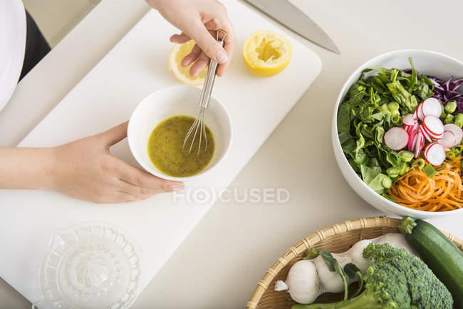 Jovem mulher preparando um molho de salada fresca — Fotografia de Stock