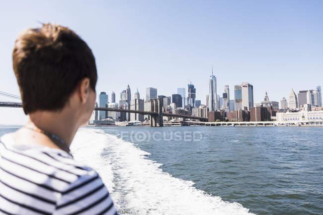 USA, New York, donna in traghetto con lo skyline di Manhattan sullo sfondo — Foto stock