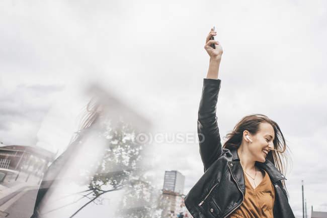 Jovem feliz com telefones no ouvido e telefone celular — Fotografia de Stock