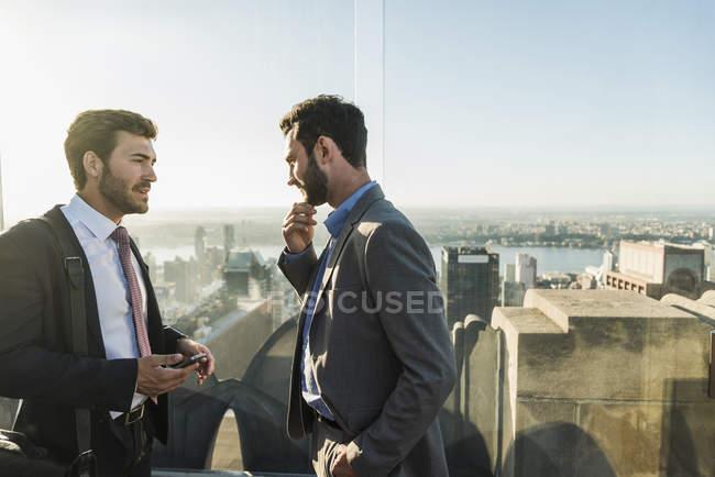 Etats-Unis, New York, deux hommes d'affaires discutant sur le pont d'observation du Rockefeller Center — Photo de stock