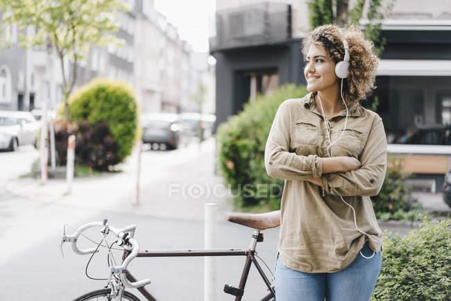 Mujer en la ciudad escuchando música con auriculares - foto de stock