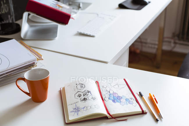 Notebook with sketch and cup of coffee on desk in office — Stock Photo