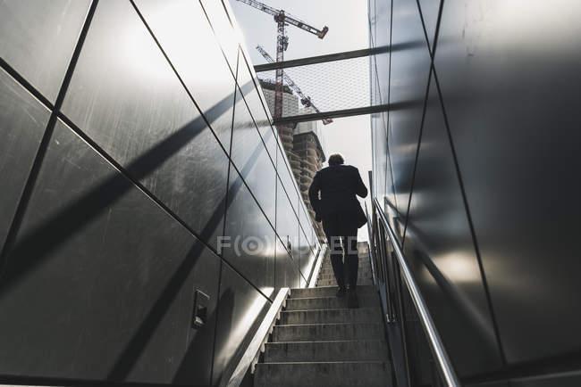 Homme d'affaires marchant sur l'escalier dans la ville — Photo de stock