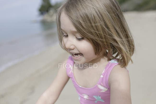 Портрет щасливої маленької дівчинки, що грає на пляжі. — стокове фото