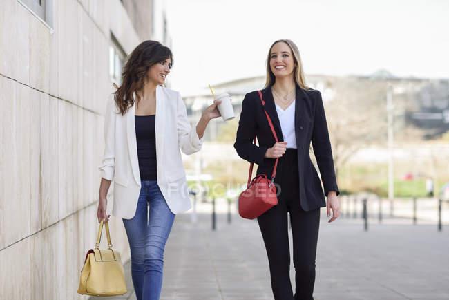 Две улыбающиеся деловые женщины с сумочками и кофе идут гулять по тротуару — стоковое фото
