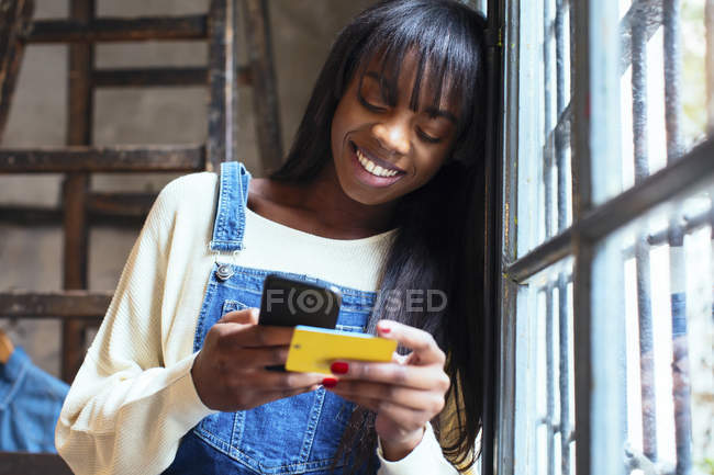 Portrait of laughing woman leaning against window looking at cell phone — Stock Photo