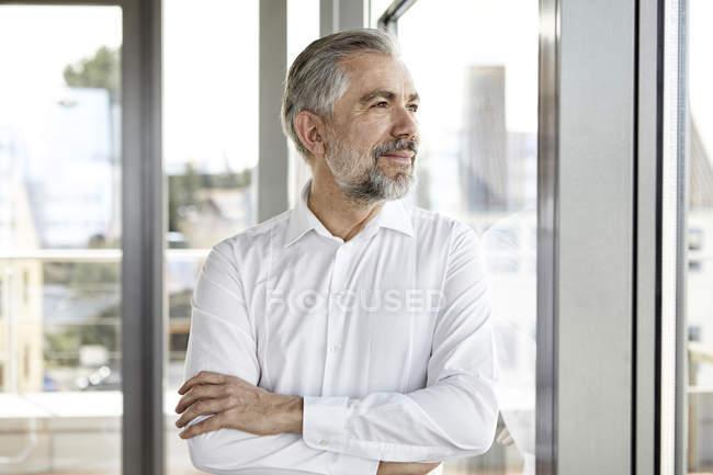 Retrato de un hombre de negocios sonriente mirando por la ventana - foto de stock