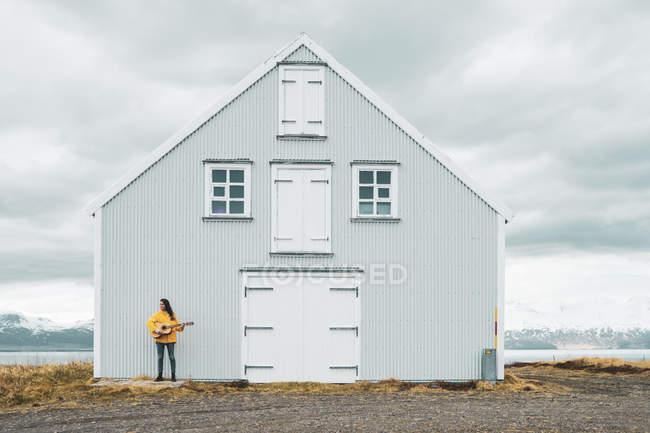 Islande, femme jouant de la guitare à la maison solitaire — Photo de stock