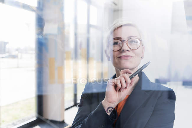 Portrait of confident businesswoman behind glass pane in office — Stock Photo