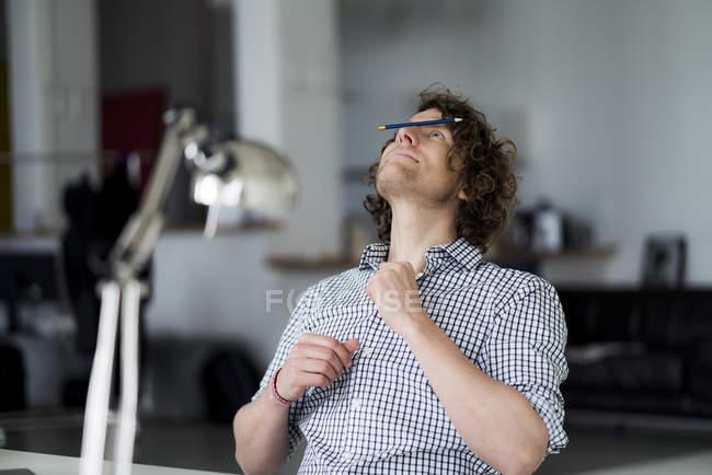 Homme d'affaires équilibrage crayon sur son visage — Photo de stock