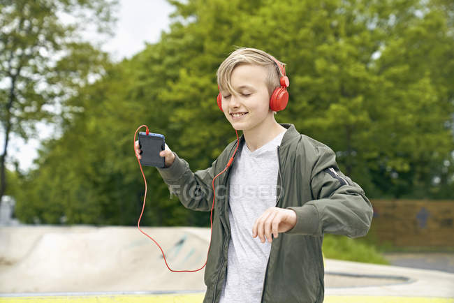 Boy with headphone dancing while listing to music on smartphone — Stock Photo