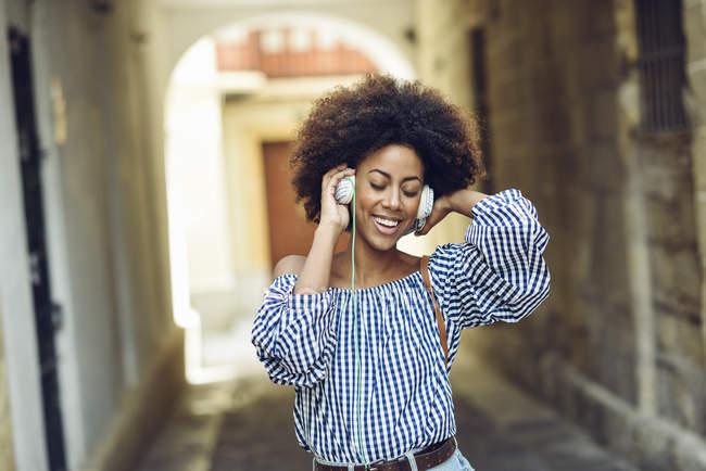 Porträt einer glücklichen jungen Frau, die mit Kopfhörern Musik hört — Stockfoto