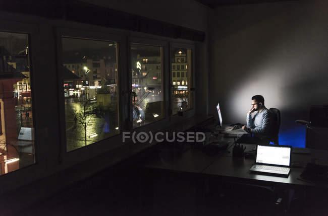 Homme d'affaires travaillant sur ordinateur au bureau la nuit — Photo de stock