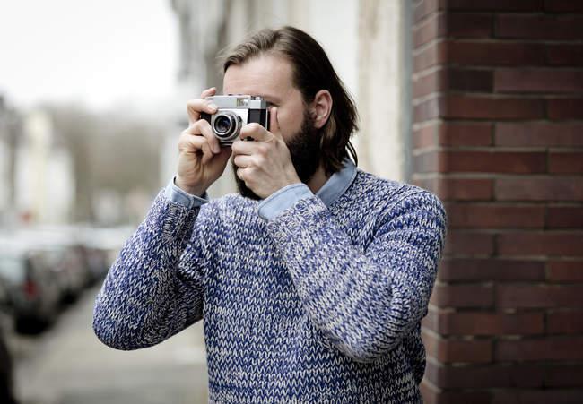 Homem com barba tirando fotos com câmera velha — Fotografia de Stock