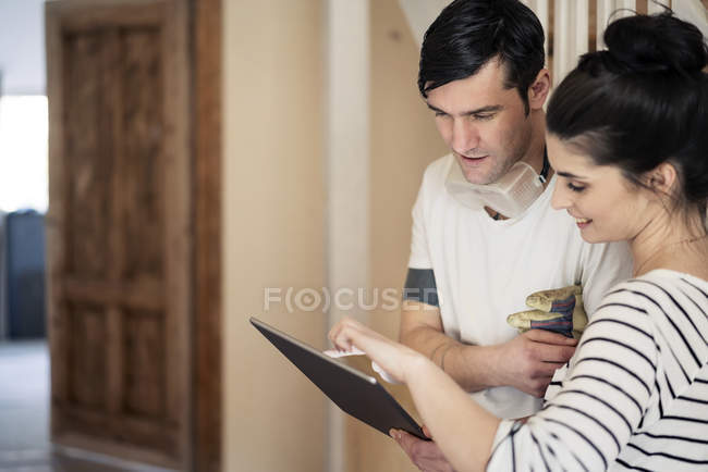 Young couple refurbishing new home, using digital tablet — Stock Photo