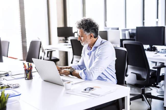 Зрелый бизнесмен, работающий за столом с ноутбуком в офисе — стоковое фото