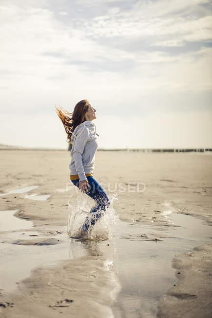 Femme heureuse s'amusant à la plage, sautant, éclaboussant de l'eau — Photo de stock
