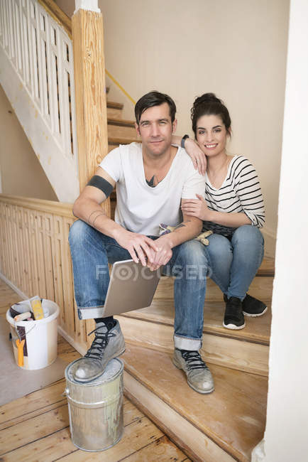 Young couple refurbishing new home, sitting on stairs using digital tablet — Stock Photo