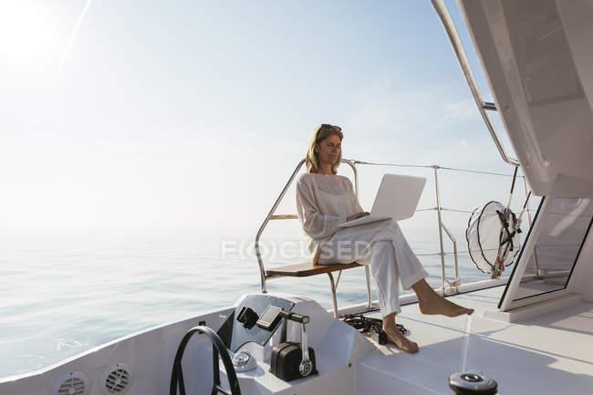 Жінка сидить на катамарані, використовуючи ноутбук — стокове фото