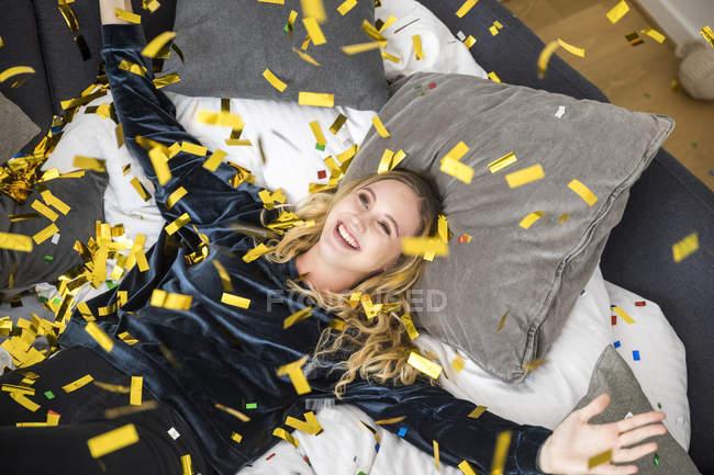 Портрет щасливої молодої жінки з літаючим конфетті вдома — стокове фото