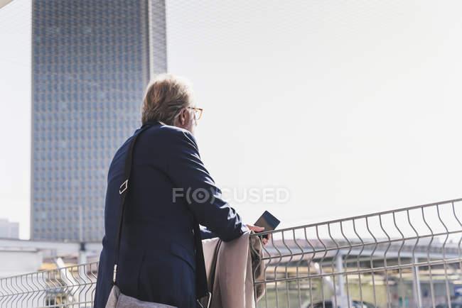 Зрелый бизнесмен в городе оглядывается по сторонам — стоковое фото