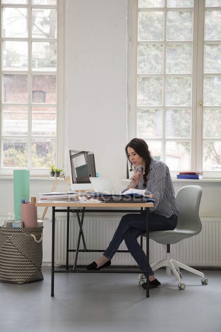 Woman working at desk in a loft office — Stock Photo