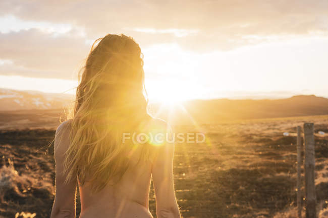 Iceland, rear view of naked young woman at sunset — Stock Photo