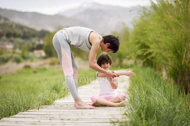 Mother explaining yoga position to daughter on boardwalk — Stock Photo