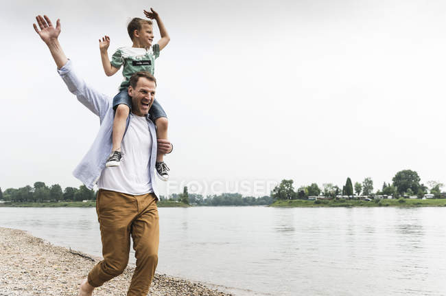 Happy father carrying son on shoulders at the riverside — Stock Photo